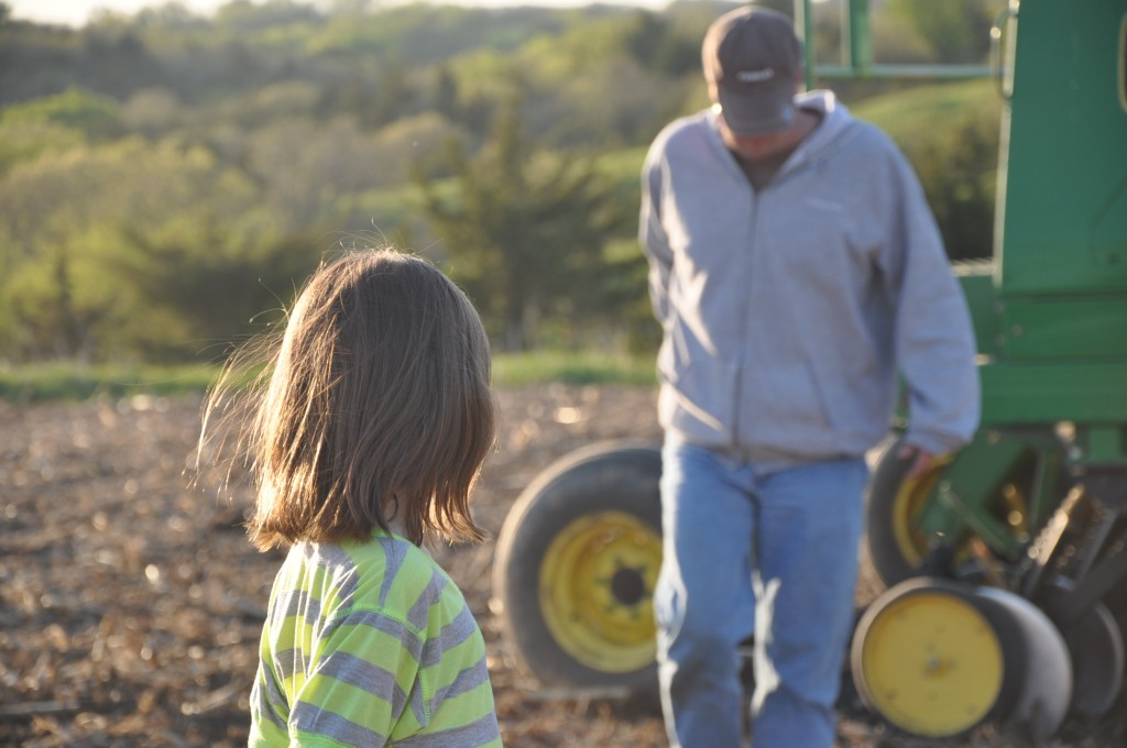 Daughter waits for farmer father in the Iowa beanfield