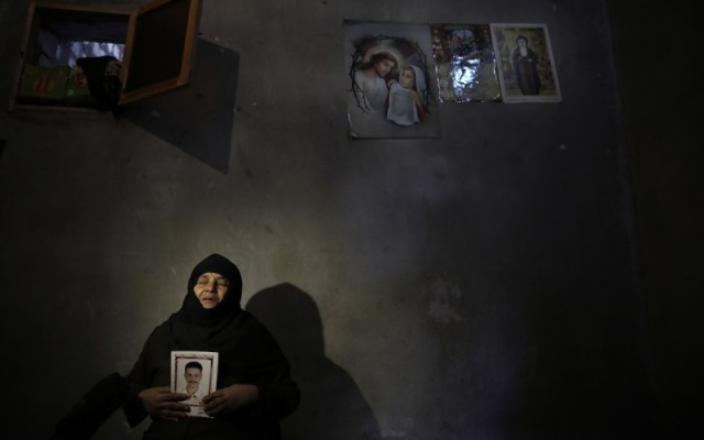 A mother of one of the victims holds her son's picture. (From the Catholic Herald)